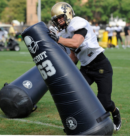 Defensive Lineman Casey Walker, 92, pounds on a tackling dummy during a rush passing drill at the University of Colorado football practice on Wednesday morning<br /> Photo by Paul Aiken  August 10, 2011.