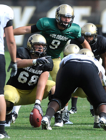 Center Shawn Daniels, 68 points out something the defense is doing to Quarterback Tyler Hansen at the University of Colorado football practice on Wednesday morning<br /> Photo by Paul Aiken  August 10, 2011.