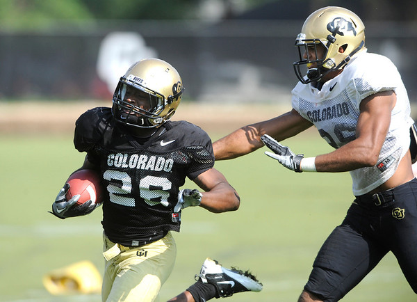 Toney Jones, 26, runs away from Ray Polk, 26, at the University of Colorado football practice on Wednesday morning<br /> Photo by Paul Aiken  August 10, 2011.