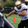 Defensive Lineman Curtis Cunningham, 50, pounds on a tackling dummy during a rush passing drill at the University of Colorado football practice on Wednesday morning<br /> Photo by Paul Aiken  August 10, 2011.