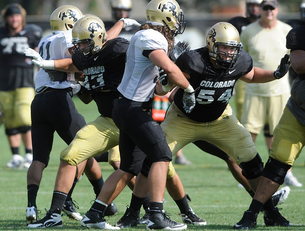 Matt Bahr, 43, and Kaiwi Crabb protect the quarterback at the University of Colorado football practice on Wednesday morning<br /> Photo by Paul Aiken  August 10, 2011.