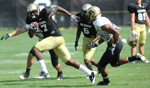 "Wide Receiver Toney Clemons, 17, tries to run away from Defensive Back Ray Polk, 26, during the University of Colorado football practice on Wednesday morning<br /> Photo by Paul Aiken  August 10, 2011.<br /> FOR MORE PHOTOS AND VIDEO INTERVIEWS FROM PRACTICE GO TO  <a href=""http://WWW.DAILYCAMERA.COM"">http://WWW.DAILYCAMERA.COM</a> AND BUFFZONE. COM"