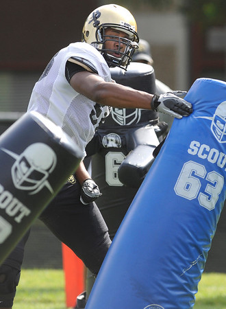 Defensive Lineman Andre Nichols, 58, pounds on a tackling dummy during a rush passing drill at the University of Colorado football practice on Wednesday morning<br /> Photo by Paul Aiken  August 10, 2011.