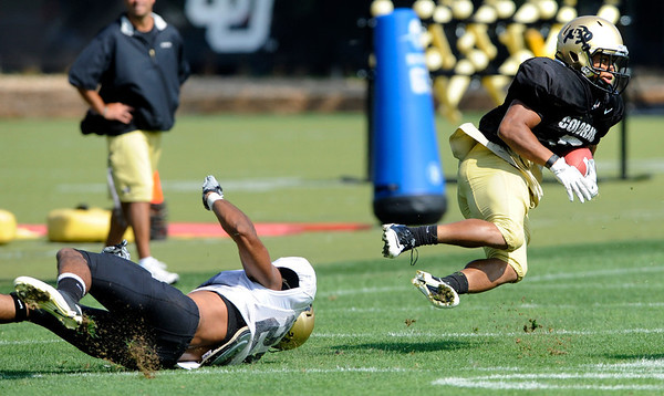 "Tailback Rodney Smith, 5, gets tripped up by Defensive Back Ray Polk, 26 during the University of Colorado football practice on Wednesday morning<br /> Photo by Paul Aiken  August 10, 2011.<br /> FOR MORE PHOTOS AND VIDEO INTERVIEWS FROM PRACTICE GO TO  <a href=""http://WWW.DAILYCAMERA.COM"">http://WWW.DAILYCAMERA.COM</a> AND BUFFZONE. COM"