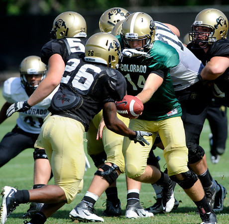 "John Schrock, 14, hands off to Tony Jones, 26, during the University of Colorado football practice on Wednesday morning<br /> Photo by Paul Aiken  August 10, 2011.<br /> <br /> FOR MORE PHOTOS AND VIDEO INTERVIEWS FROM PRACTICE GO TO  <a href=""http://WWW.DAILYCAMERA.COM"">http://WWW.DAILYCAMERA.COM</a> AND BUFFZONE. COM"