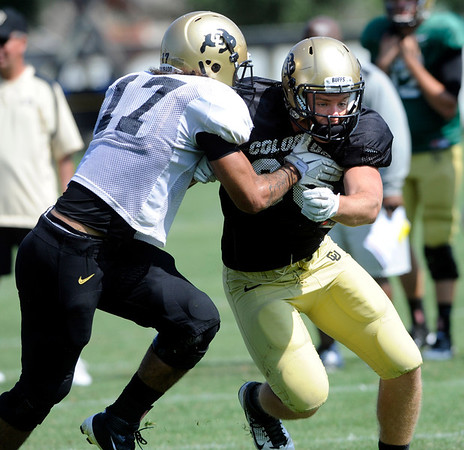 Kyle Slavin, 88 tries to fight through Josh Hartigan, 17, at the University of Colorado football practice on Wednesday morning<br /> Photo by Paul Aiken  August 10, 2011.