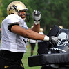 Defensive Lineman Kirk Poston, 91, pounds on a tackling dummy during a rush passing drill at the University of Colorado football practice on Wednesday morning<br /> Photo by Paul Aiken  August 10, 2011.