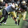 Douglas Rippy, 2, reaches out to tackle Rodney Stewart, 5, at the University of Colorado football practice on Wednesday morning<br /> Photo by Paul Aiken  August 10, 2011.