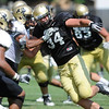 Ryan Deehan, 34 tries to fight past Anthony Perkins, 7 at the University of Colorado football practice on Wednesday morning<br /> Photo by Paul Aiken  August 10, 2011.