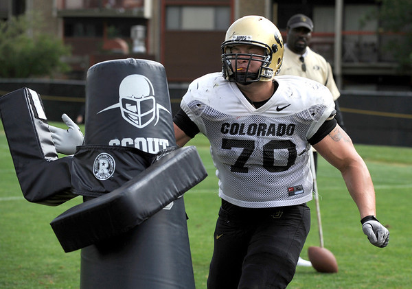Defensive Lineman Eric Richter, 70, pounds on a tackling dummy during a rush passing drill at the University of Colorado football practice on Wednesday morning<br /> Photo by Paul Aiken  August 10, 2011.