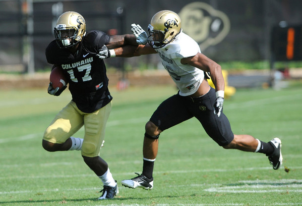 """Wide Receiver Toney Clemons, 17, tries to fend off Defensive Back Ray Polk, 26, during the University of Colorado football practice on Wednesday morning<br /> Photo by Paul Aiken  August 10, 2011.<br /> FOR MORE PHOTOS AND VIDEO INTERVIEWS FROM PRACTICE GO TO  <a href=""""http://WWW.DAILYCAMERA.COM"""">http://WWW.DAILYCAMERA.COM</a> AND BUFFZONE. COM"""
