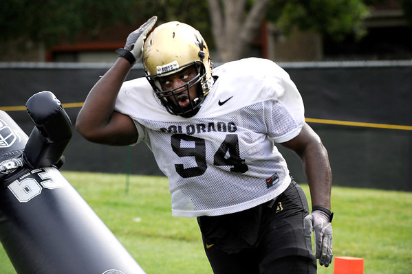 Defensive Lineman Nate Bonsu, 94, pounds on a tackling dummy during a rush passing drill at the University of Colorado football practice on Wednesday morning<br /> Photo by Paul Aiken  August 10, 2011.