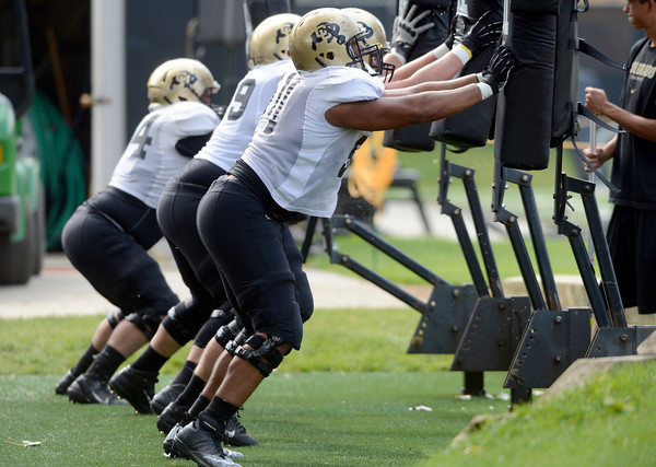 """Kirk Poston (91) hits a sled with his defense teammates during the University of Colorado football team practice on Monday August 20, 2012. <br /> For more photos go to  <a href=""""http://www.buffzone.com"""">http://www.buffzone.com</a><br /> Photo by Paul Aiken / The Boulder Camera"""