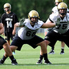 0805cufb262.JPG Ethan Adkins, #63, Shawn Daniels, #68, and #75 Jack Harris work a blocking drill during the CU football practice on Thursday, Aug. 5.<br /> Jeremy Papasso/ Camera