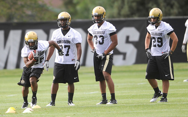 University of Colorado's Tony Jones (left) weaves through the cones while Trea Jones (middle left), Cordary Allen (middle right) an Justin Torres (right) wait for their chance during football practice Thursday. ( MARK LEFFINGWELL )