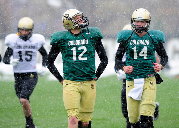 """Quarterback Stevie Joe Dorman (12) looks up to the sky as the snow falls heavily during the University of Colorado football team practice on the CU Boulder Campus on  Tuesday April 3, 2012. With Dorman is quarterback John Schrock (14).<br /> For more photos of the practice go to  <a href=""""http://www.buffzone.com"""">http://www.buffzone.com</a><br /> Photo by Paul Aiken / The Camera"""