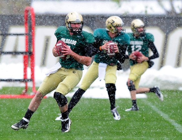 """From left to right Quarterbacks Connor Wood (5), John Schrock (14) and Stevie Joe Dorman (12) work together during a drill during the University of Colorado football team practice on the CU Boulder Campus on  Tuesday April 3, 2012.<br /> For more photos of the practice go to  <a href=""""http://www.buffzone.com"""">http://www.buffzone.com</a><br /> Photo by Paul Aiken / The Camera"""