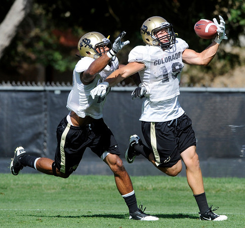 Travis Sandersfeld, 19, pulls in a pass with Ray Polk, 26, covering in a pass coverage drill with the defense during the Monday August 22, 2011 CU football team practice.<br /> <br /> Photo by Paul Aiken / The Camera / August 22 2011