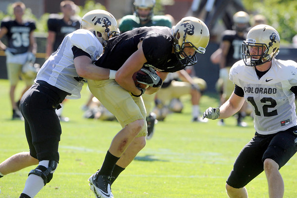 "Parker Orms, 13, wraps up Tyler McCulloch, 87, as Patrick Mahnke, 12 moves in during the University of Colorado Buffalos  Monday August 15 practice. FOR MORE PHOTOS AND VIDEO INTERVIEWS FROM THE PRACTICE GO TO  <a href=""http://WWW.BUFFZONE.COM"">http://WWW.BUFFZONE.COM</a> OR  <a href=""http://WWW.DAILYCAMERA.COM"">http://WWW.DAILYCAMERA.COM</a><br /> Photo by Paul Aiken / The Camera / 8/ 15/ 11"