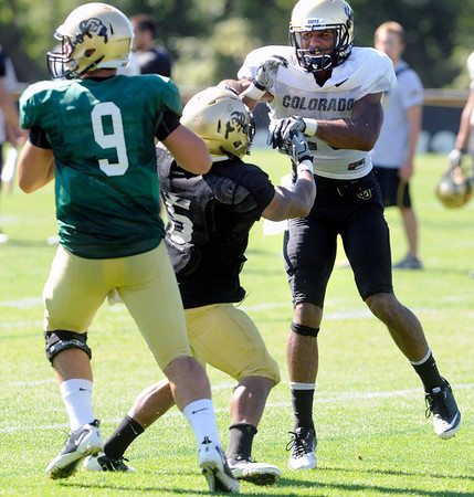 """Rodney Stewart, 5, keeps Ray Polk, 26, away from Tyler Hansen, 9,  during the University of Colorado Buffalos  Monday August 15 practice. FOR MORE PHOTOS AND VIDEO INTERVIEWS FROM THE PRACTICE GO TO  <a href=""""http://WWW.BUFFZONE.COM"""">http://WWW.BUFFZONE.COM</a> OR  <a href=""""http://WWW.DAILYCAMERA.COM"""">http://WWW.DAILYCAMERA.COM</a><br /> Photo by Paul Aiken / The Camera / 8/ 15/ 11"""