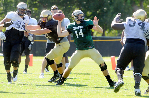 "John Schrock, 14, throws under pressure from Nate Bonsu, 94, during the University of Colorado Buffalos  Monday August 15 practice. FOR MORE PHOTOS AND VIDEO INTERVIEWS FROM THE PRACTICE GO TO  <a href=""http://WWW.BUFFZONE.COM"">http://WWW.BUFFZONE.COM</a> OR  <a href=""http://WWW.DAILYCAMERA.COM"">http://WWW.DAILYCAMERA.COM</a><br /> Photo by Paul Aiken / The Camera / 8/ 15/ 11"