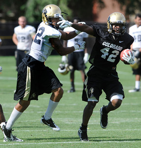 Josh Ford, 42, gives a stiff arm to Paul Vigo during the University of Colorado football team practice in Boulder  on Thursday August 11, 2011. For more photos and video interviews from the practice go to www.dailycamera.com Photo by Paul Aiken  August 11, 2011.