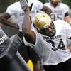 "Nate Bonsu shoves aside a tackling dummy during a pass rushing drill during the University of Colorado football team practice in Boulder  on Thursday August 11, 2011.<br /> For more photos and video interviews from the practice go to  <a href=""http://www.dailycamera.com"">http://www.dailycamera.com</a><br /> Photo by Paul Aiken  August 11, 2011."
