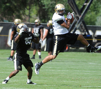 K.T. Tu'umalo, 42,  makes and interception in front of Austin Vincent, 81, during the University of Colorado football team practice in Boulder  on Thursday August 11, 2011. For more photos and video interviews from the practice go to www.dailycamera.com Photo by Paul Aiken  August 11, 2011.