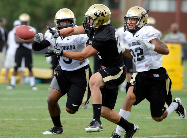 "Nelson Spruce, 22, hauls in a touchdown pass while being covered by  Douglas Rippy, 3, at left and Paul Vigo, 32, during the University of Colorado football team practice in Boulder  on Thursday August 11, 2011.<br /> For more photos and video interviews from the practice go to  <a href=""http://www.dailycamera.com"">http://www.dailycamera.com</a><br /> Photo by Paul Aiken  August 11, 2011."