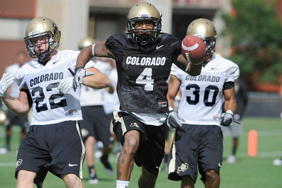 Keenan Canty, 4, leaps into the end zone while running awy from Arthur Jaffee, 22, Jermane Clarke, 30, during the University of Colorado football team practice in Boulder  on Thursday August 11, 2011. For more photos and video interviews from the practice go to www.dailycamera.com Photo by Paul Aiken  August 11, 2011.