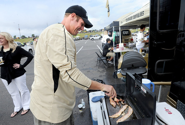 "Marshall Carpenter of Denver is making bacon during the CU-CSU pregame tailgating at Sports Authority Field.<br /> For more photos of the CU game, go to  <a href=""http://www.dailycamera.com"">http://www.dailycamera.com</a>.<br />  Cliff Grassmick / September 17, 2011"