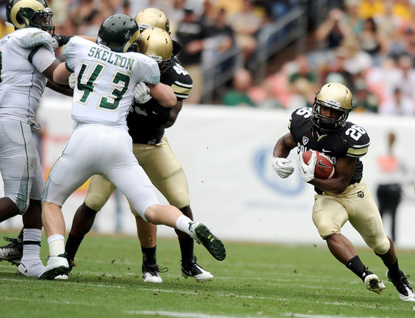 "University of Colorado's Tony Jones breaks through the line while rushing the ball during a football game against Colorado State University on Saturday, Sept. 17, at Sports Authority Field in Denver. CU defeated CSU 28-14. For more photos of the game go to  <a href=""http://www.dailycamera.com"">http://www.dailycamera.com</a><br /> Jeremy Papasso/ Camera"