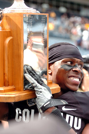 "University of Colorado's Ayodeji Olatoye holds up the Centennial Trophy after winning the Rocky Mountain Showdown football game against Colorado State University on Saturday, Sept. 17, at Sports Authority Field in Denver. CU defeated CSU 28-14. For more photos of the game go to  <a href=""http://www.dailycamera.com"">http://www.dailycamera.com</a><br /> Jeremy Papasso/ Camera"