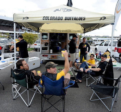 "Jeremy DuPont, center, salutes the Buffs during the CU-CSU pregame tailgating with friends at Sports Authority Field.<br /> For more photos of the CU game, go to  <a href=""http://www.dailycamera.com"">http://www.dailycamera.com</a>.<br />  Cliff Grassmick / September 17, 2011"