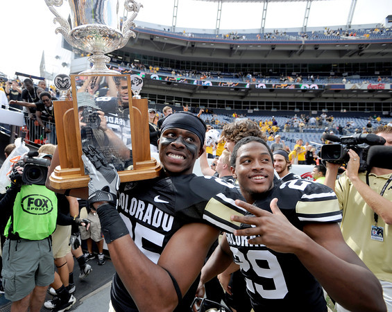 "Ayodeji Olatoye,  and Josh Ford (29), both of CU,  walk off with the Centennial Trophy after beating CSU.<br /> For more photos of the CU game, go to  <a href=""http://www.dailycamera.com"">http://www.dailycamera.com</a>.<br />  Cliff Grassmick / September 17, 2011"