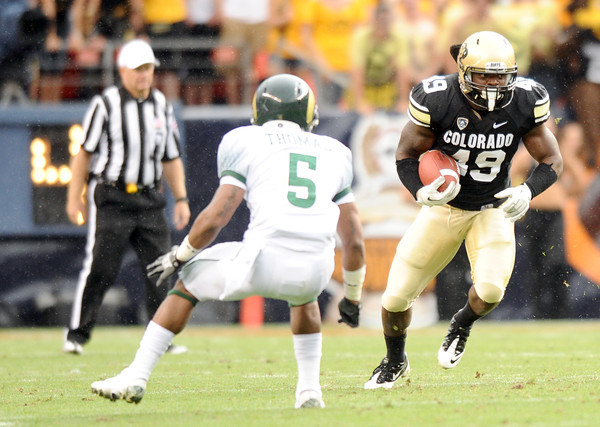 "University of Colorado's Evan Harrington rushes the ball past Colorado State's Momo Thomas during a football game against Colorado State University on Saturday, Sept. 17, at Sports Authority Field in Denver. CU defeated CSU 28-14. For more photos of the game go to  <a href=""http://www.dailycamera.com"">http://www.dailycamera.com</a><br /> Jeremy Papasso/ Camera"