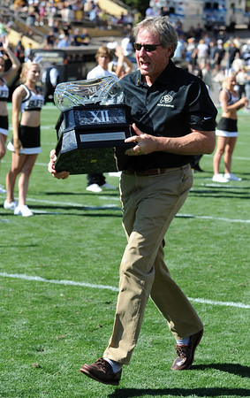 """Former CU head coach Gary Barnett runs the 2001 BIG 12 trophy over to that team during halftime.<br /> For more photos of the CU game, go to  <a href=""""http://www.dailycamera.com"""">http://www.dailycamera.com</a>.<br /> Cliff Grassmick / September 10, 2011"""