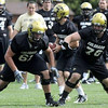 Offensive linemen Scott Fernandez, left, and Gus Handler, right, block for quarterback Tyler Hansen, center, at practice on Saturday, Aug. 15, 2009 at the CU practice fields. Photo by Mara Auster/Daily Camera