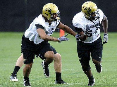 Inside linebacker Marcus Burton runs by inside linebacker Josh Harigan during drills at practice on Saturday, Aug. 15, 2009 at the CU practice fields. Photo by Mara Auster/Daily Camera