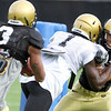 University of Colorado's Jared Bell (right) tries to get by Andre Simmons (center) to tackle Jimmy Smith (left) during football practice in Boulder, Colorado August 9, 2010.  CAMERA/Mark Leffingwell