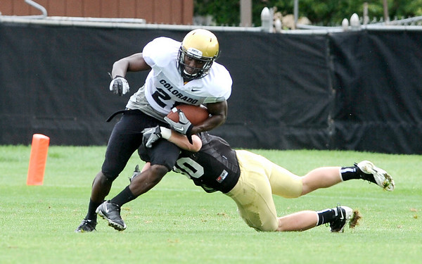 University of Colorado's Brian Lockridge (left) breaks a tackle from Parker Orms (right) during football practice in Boulder, Colorado August 9, 2010.  CAMERA/Mark Leffingwell