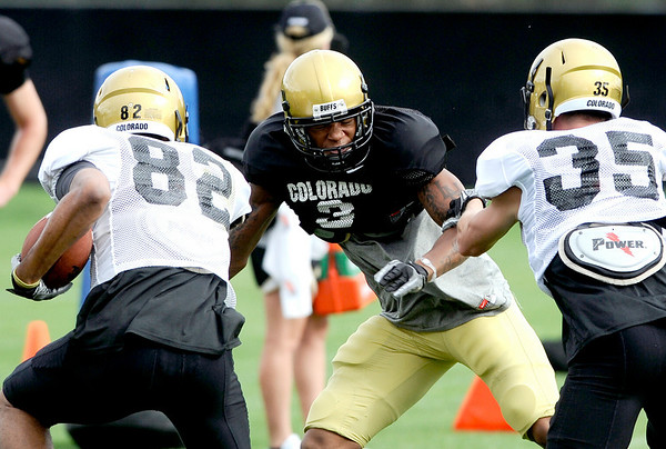 University of Colorado's Jarrod Darden (left) and Kyle Cefalo (right) try to block Jimmy Smith (center) during football practice in Boulder, Colorado August 9, 2010.  CAMERA/Mark Leffingwell