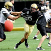 University of Colorado safety Matt Meyer (center) pushes off Jarrod Darden (left) to tackle Kyle Cefalo (right) during football practice in Boulder, Colorado August 9, 2010.  CAMERA/Mark Leffingwell
