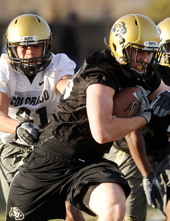 """Kyle Slavin tries to get away from Terrel Smith during CU practice.<br /> For a videos and photos of the practice, go to  <a href=""""http://www.dailycamera.com"""">http://www.dailycamera.com</a>.<br /> Cliff Grassmick/ March 11, 2011"""
