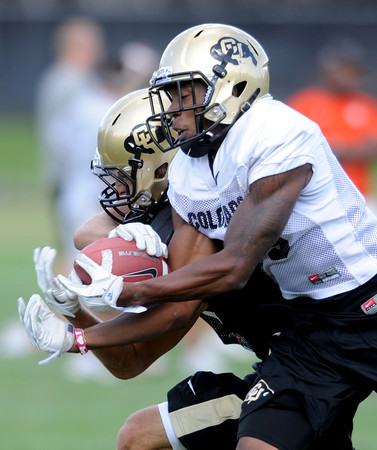 """Josh Moten, right, takes the ball away from Dustin Ebner during drills.<br /> For more photos and a video from CU football today, go to  <a href=""""http://www.dailycamera.com"""">http://www.dailycamera.com</a>.<br /> Cliff Grassmick / August 17, 2011"""