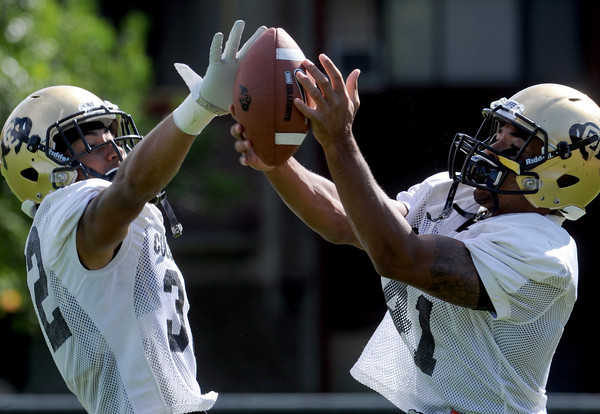"Paul Vigo, left, and Terrel Smith go for the ball during a DB drill on Wednesday.<br /> For more photos and a video from CU football today, go to  <a href=""http://www.dailycamera.com"">http://www.dailycamera.com</a>.<br /> Cliff Grassmick / August 17, 2011"