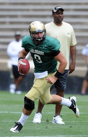 "CU QB, Tyler Hansen, rolls out as coach Jon Embree watches on Friday.<br /> For more photos and videos from Friday, go to  <a href=""http://www.dailycamera.com"">http://www.dailycamera.com</a><br /> Cliff Grassmick / August 19, 2011"