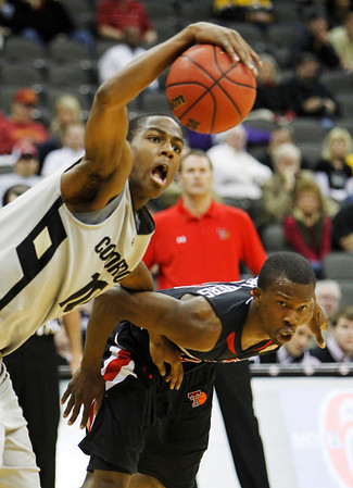 Colorado guard Alec Burks (10) reaches for the ball while covered by  Texas Tech guard David Tairu (13) during the first half of an NCAA college basketball game at the Big 12 Conference Tournament on Wednesday, March 10, 2010, in Kansas City, Kan. (AP Photo/Charlie Neibergall)