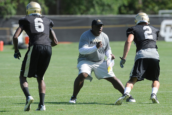 """Coach Eric Bieniemy, lines us against Logan Gray, 2, and Paul Richardson, 6, during the University of Colorado Football team practice on Friday August 12, 2011.<br /> For more photos and video interviews from the practice go to  <a href=""""http://www.buffzone.com"""">http://www.buffzone.com</a> and dailycamera.com<br /> Photo by Paul Aiken  August 12,  2011."""