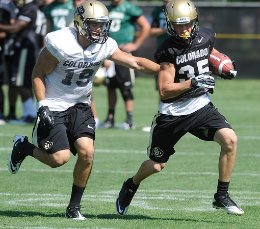 """Kyle Cefano, 35, runs away from Travis Sandersfeld, 19, during a passing drill at  the University of Colorado Football team practice on Friday August 12, 2011.<br /> For more photos and video interviews from the practice go to  <a href=""""http://www.buffzone.com"""">http://www.buffzone.com</a> and dailycamera.com<br /> Photo by Paul Aiken  August 12,  2011."""